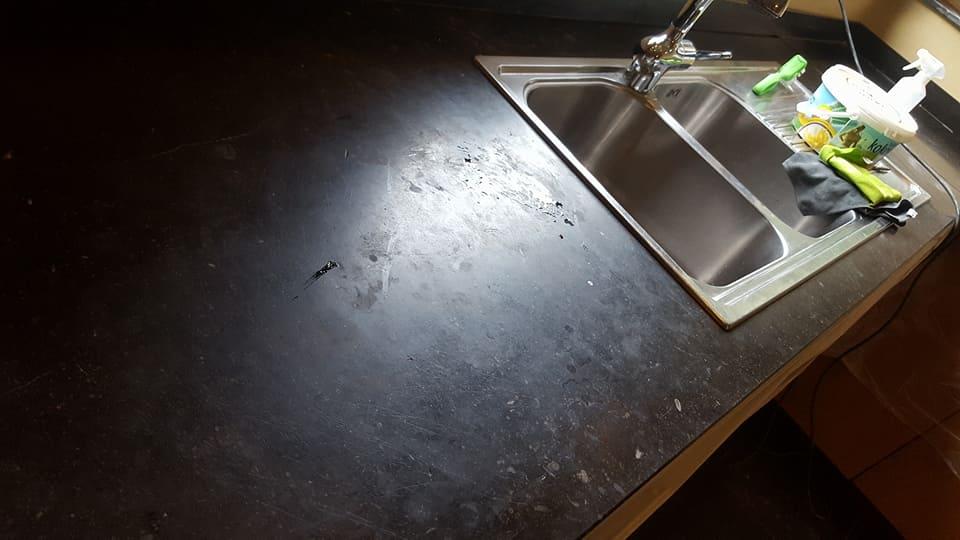 Keukenaanrecht van blauwe hardsteen met kalkvlekken